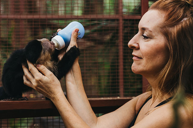 Woman feeding a capuchin monkey